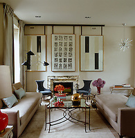 A triptych by Josep Vallribera is hung on a sliding mount that conceals the television in this part of the elegant living room