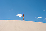A woman high on a dune with her white  scarf blowing in the breeze.<br />