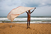 A sadhu (Hindu Holy man) dries off his dhoti (sarong) on Puri Beach along the Bay of Bengal in Puri, Orissa, India. A dip in its salty waters is believed to hold great religious significance, as a result these golden sand beaches sees is a never-ending rush of pilgrims and tourists. Photo: Sanjit Das/Panos