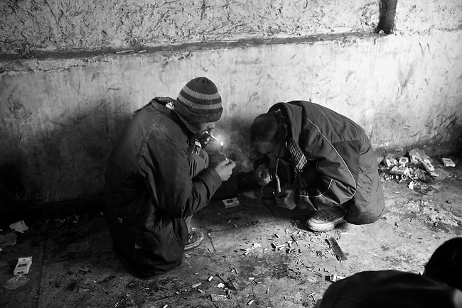 Two men smoke opium inside the ruins of the former Soviet Cultural Center in Kabul, Afghanistan. More than 90 percent of the world's opium--from which heroin is derived--comes from Afghanistan, and its cheap availability is wreaking havoc on a society already ravaged by 30 years of war. As many as 2,000 addicts gather each day to get high inside the derelict structure, which was almost completely destroyed during the 1992-1994 civil war. Feb. 2, 2009.