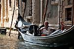 A gondolier takes a break in his gondola in Venice, Italy