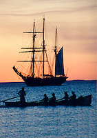 A Cottesloe beach surf boat crew row past the Leeuwin 2 at sunset.