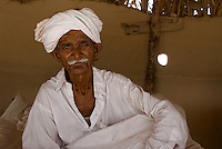 An elderly Pakistani man in his home.