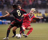 Kelly Parker of Canada tries to split a pair of Mexico defenders in the CONCACAF Olympic Qualifying semifinal match at BC Place in Vancouver, B.C., Canada Friday Jan. 27, 2012. Canada won the match 3-1 to earn a berth in 2012 London Olympics.