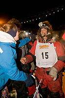 Lance Mackey is greeted by wife at the finish line in Nome. Mackey took third place and arrived with a damaged sled and injured dog named Zoro, due to a snow machine collision about 20 miles from the finish line.