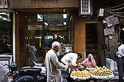 A fruit vendor sets up a stall right outside a jewellery stores in Dariba Kalan, Old Delhi, India. Photo: Sanjit Das/Panos Pictures