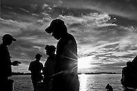 Silhouettes of young men seen during the sunset over the Amazon river in the port of Tabatinga, Brazil, 21 April 2004. Amazonia is the world's largest dense tropical forest area. Since the 16th century the original indigenous people have been virtually pushed away or exterminated. The primal ancient unity between tribes and the jungle ambient has changed into a fight between the urban based civilization and the jungle enviroment. Although new generations of white and mestizo settlers have not become adapted to the wild tropical climate and rough conditions, they keep moving deeper into the virgin forest. The technological expansion causes that Amazonia is changing rapidly.