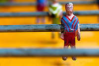A table football player figure, with a painted red and blue shirt, is seen inside the table football box on the street of Olmedo, a small village in the mountains of Ecuador, 27 June 2010. Table football, also known as futbolin in Latin America, is a widely popular table-top game in Ecuador. During the annual fairs, the rusty old outdoor-designed tables, fully ocuppied by excited children, may be found on all public places, particularly on the squares and in the parks. Human players use figures mounted on rotating bars to kick the small plastic ball into the opposing goal. Each team of 1 or 2 human players controls 4 rows on its side of the table. The game ends when one team scores a predetermined number of goals. In 2002, the International Table Soccer Federation (ITSF) was established to promote the sport of table football.