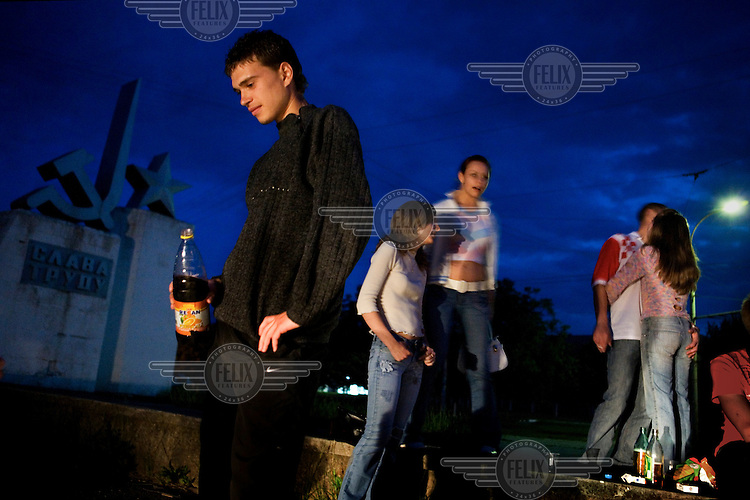 Young Transnistrians drink homemade wine as they gather in a park during their summer break from university. The communist hammer and sickle emblem, still featuring in Transnistria's flag looms in the darkness behind them. Also known as Trans-Dniestr or Transdniestria, Transnistria, located mostly on a strip of land between the Dniester River and the eastern Moldovan border with Ukraine, broke away from Moldova in 1990 and although a de facto independent state, governed by the Pridnestrovian Moldavian Republic (PMR), is not recognised internationally.