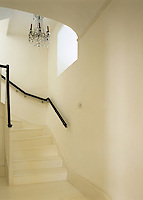 A dramatic black banister makes a bold statement on this white painted wooden staircase
