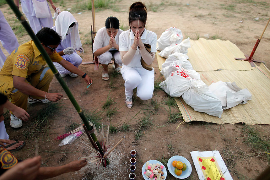 People pray next to bags with unclaimed human remains taken out of graves during a Thai Chinese ceremony at the Mang Teung Sua Jung Cemetery in Chonburi province southeast of Bangkok March 18, 2012. Every 10 years, hundreds of people wearing white, a customary colour for funerals and visiting temples, gather at this cemetery to exhume and cremate corpses as they believe they are helping the dead who have no friends or relatives. The ashes of the unclaimed bodies are spread on the sea to make room at the burial ground for more unclaimed bodies in the coming years. The tradition originated 90 years ago after diseases like Malaria killed many Thais of Chinese descent living in Chonburi.  REUTERS/Damir Sagolj (THAILAND)