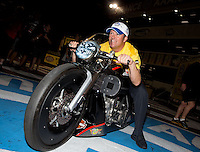 Nov 10, 2013; Pomona, CA, USA; NHRA pro stock driver Jeg Coughlin Jr sits on the pro stock motorcycle of Eddie Krawiec (not pictured) following the Auto Club Finals at Auto Club Raceway at Pomona. Mandatory Credit: Mark J. Rebilas-USA TODAY