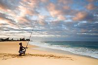 Hawaiian Surf fisherman at sunrise at Kekaka Beach on the island of Kauai Hawaii