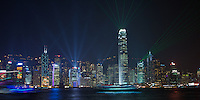 The skyscrapers along Hong Kong island's harbour waterfront at night, with fa&ccedil;ades covered with decorative lighting designs for Christmas and laser searchlights for the nightly Symphony of Lights show