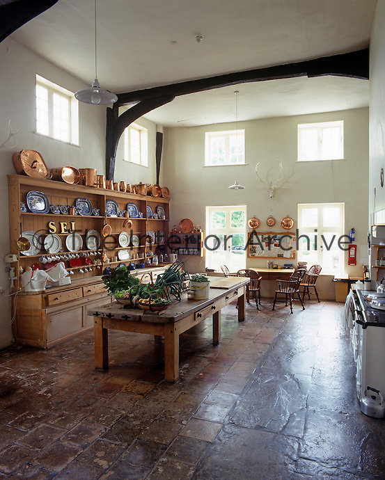 A large country kitchen has a double-height ceiling and is furnished with a vast wooden dresser and long table