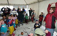 Linda K. Creech of Lakeland, Fla., leads children in song inside a tent run by the Chugach Baptist Association's Salmon Frenzy missionary outreach at the mouth of the Kenai River in Kenai, Alaska. Missionaries from at least a dozen states volunteer services to Alaskan residents as they dipnet salmon at the river's mouth each July.