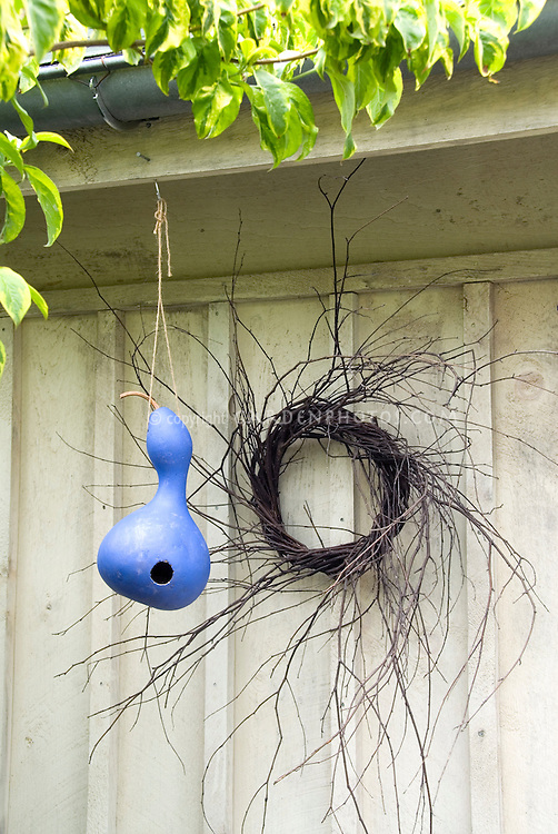 Birds nest gourd with wreath on shed wall