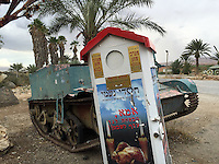 10. &quot;Charity for the Orphans and Widows&quot;: alms box with abandoned tank outside cafe, Jordan Valley.<br /> <br /> Maintained by the Charities of Naomi, this alms box is designed for weekly collection of non-perishable foodstuffs for orphans and widows. Yet it tilts crazily as if it's been hit by the abandoned tank behind it. I was struck by the incongruity of &quot;chesed&quot; or &quot;loving kindness,&quot; paired with the violent legacy of the tank. Moreover, the picture of the plump roasted chicken with candles is accompanied by these words:  &quot;Mother, you promised us a chicken for the Sabbath.&quot; If the children are orphaned and the mother widowed, this is indeed a grim reminder of the casualties of war.
