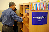 United States President Barack Obama assists in putting in book shelves as he joins volunteers in a library as they participate in a service project, at Browne Education Center, in Washington, DC, USA, on the Martin Luther King Jr national holiday, 16 January 2012. The project was in memory of the legacy of community service, promoted by the late civil rights leader, who was assassinated in 1968..Credit: Mike Theiler / Pool via CNP