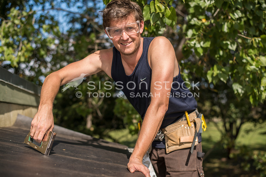 Home handyman wearing safety glasses and stapling building paper to a roof, New Zealand- stock photo, canvas, fine art print