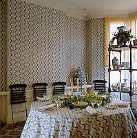 The walls of this dining room are lined with a batik-style patterned wallpaper which matches the tablecloth