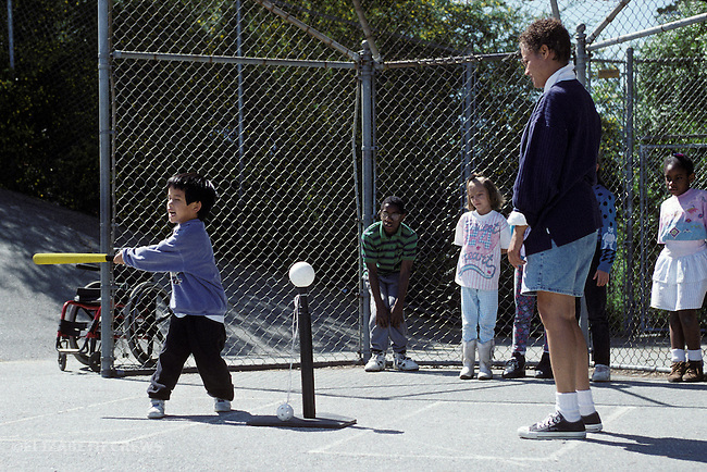 """Oakland, CA Adaptive P.E. teacher supervising learning handicapped students with """"T"""" ball play"""
