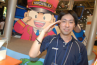 A member of staff on the booth for software maker Hudson. The character behind him is a train driver.