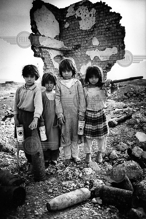 DELIZIAN, KURDISTAN, IRAQ, OCTOBER 1993. Young children collect copper and aluminium by chopping it from unexploded ordnance in an old ammunition bunker. They sell it for 10 dollarcent per kilo. Twenty million landmines and unexploded ordnance litter the former frontline in the Iran vs Iraq War still killing and maim ing Kurdish people on a daily basis..©Photo by Frits Meyst/Panos Pictures