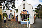"Portmeirion, in North Wales, is a resort, where no one has ever lived. A self-taught Welsh architect named Sir Clough Williams-Ellis built it out of architectural salvage between the 1920s and 1970s, loosely based on his memories of trips to Portofino. Including a pagoda-shaped Chinoiserie gazebo, some Gothic obelisks, eucalyptus groves, a crenellated castle, a Mediterranean bell tower, a Jacobean town hall, and an Art Deco cylindrical watchtower. He kept improving Portmeirion until his death in 1978, age 94. It faces an estuary where at low tide one can walk across the sands and look out to sea. At high tide, the sea is lapping onto the shores. Every building in the village is either a shop, restaurant, hotel or self-catering accomodation. The village is booked out at high season, with numerous wedding receptions at the weekends. Very popular amongst the English and Welsh holidaymakers. Many who return to the same abode season after season. Hundreds of tourists visit every day, walking around the ornamental gardens, cobblestone paths, and shopping, eating ice-creams, or walking along the woodland and coastal paths, amongst a colourful assortment of hydrangea, rhododendrons, tree ferns and redwoods. The resort boasts two high class hotels, a la carte menus, a swimming pool, a lifesize concrete boat, topiary, pools and wishing wells. The creator describes the resort as ""a home for fallen buildings,"" and its ragged skyline and playful narrow passageways which were meant to provide ""more fun for more people."" It does just that.///The Prisoner and Pocket Money Shops. The Prisoner is a television cult series starring Patrick McGoohan filmed at Portmeirion. The Prisoner shop is his home in the TV series."