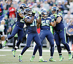 Seattle Seahawks  defenders, Earl Thomas III (29), Kam Chancellor (31) K.J. Wright  (50) and Jordan Hill (97) celebrates after Wright  sacked San Francisco 49ers quarterback Colin Kaepernick (7) at CenturyLink Field in Seattle, Washington on December 14, 2014.  Kapernick was sacked six times in the Seahawks 17-7 win  over the 49ers  © 2014. Jim Bryant Photo. All Rights Reserved.