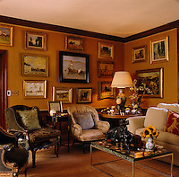 A collection of paintings hangs against the fabric covered walls of this living room which is furnished with an eclectic array of chairs