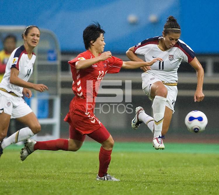USA midfielder (11) Carli Lloyd sprints past North Korea midfielder (12) Ri Un Gyong. The United States (USA) and North Korea (PRK) played to a 2-2 tie during a FIFA Women's World Cup China 2007 opening round Group B match at Chengdu Sports Center Stadium, Chengdu, China, on September 11, 2007.