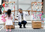 Yoshitomo Sasaki talks with a young customer who is admiring the Edo furin, or glass wind chimes, which he sells on the on the streets of chic Ginza district in Tokyo, Japan. The chimes, which date back more than 200 years in Japan, were traditionally carried around town dangling from  bamboo poles by sellers. Sasaki is one of a few people who continue this trend.