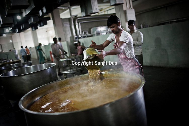Chefs prepare meals in the kitchen of the Sai Prasadalaya in Shirdi, Maharashtra, India. The Prasadalaya feeds an approximate number of 30000 Sai Baba devotees as a Prasad (holy meal) every day. Free Prasad meals are served to all the devotees. An approximate number of 1000 devotees are served everyday with this facility. Expenses for a plate of Prasad meal  is around Rs. 15/- but the Saibaba Sansthan provides prasad meals to all Sai devotees to Rs. 6/- only. The prasadalaya at the Shirdi Sai Baba Shrine is powered by a large array of concave mirrors that transform sunlight to energy to create hot water and steam for the cooking process. Photograph: Sanjit Das