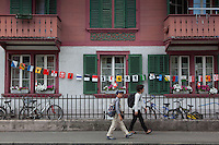 Switzerland. Canton Bern. Interlaken. Asian tourists walk on a sidewalk near a traditional wooden house with various flags from the diverse swiss cantons. Mother and son carry a backpack on their backs. 31.07.2016 © 2016 Didier Ruef