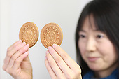 """Jan. 21, 2009; Obama, Fukui Prefecture, Japan - Chika Shimada, a clerk at the Wakasaya store, holds up a japanese confectionery with President Obama's face and """"I Love Obama"""" slogan stamped on it."""