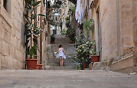 Girl on the steps of a steep narrow street in the Old Town of Dubrovnik, Croatia. The city developed as an important port in the 15th and 16th centuries and has had a multicultural history, allied to the Romans, Ostrogoths, Byzantines, Ancona, Hungary and the Ottomans. In 1979 the city was listed as a UNESCO World Heritage Site. Picture by Manuel Cohen