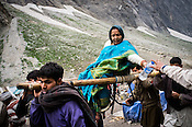 Porters carry a hindu pilgrim on the pallanquin at the base of Amarnath Cave in Kashmir, India. Hindu pilgrims brave sub zero temperature and high latitude passes and make their pilgrimage to reach the sacred Amarnath cave, which houses a lingam - a stylized phallus, worshiped by Hindus as a symbol of God Shiva. Photo: Sanjit Das/Panos