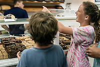 Kids making a selection in a fudge shop.