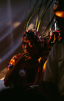 A young Zapotec woman sits in the shadows during a wedding celebration in the Chagigo neighborhood of Juchitan. Weekends are full of wedding celebrations complete with traditional food and dancing in the street..Mexico's narrowest point is the Isthmus of Tehuantepec--flat, country where the Zapotec culture is still strong.  In the Isthmus, women are noticeably open and confident, and take leading role in business and government.  The Isthmus never became part of the Aztec Empire and resistance to the Spanish was strong in the mid-1500s.