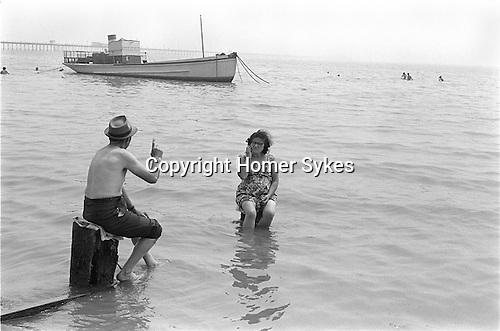 Southend-on-Sea, Essex. 1969<br /> Ignoring the incoming tide a couple discuss some of the finer points of life. Sir John Betjeman once said that, &quot;&hellip; the Pier is Southend, Southend is the Pier&quot;. It&rsquo;s the longest pier in the world extending 1.34 miles into the Thames Estuary.