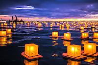Spectators at Hawai'i's Annual Lantern Floating Ceremony mark the moment at sunset, Ala Moana Beach Park, O'ahu.