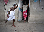 A girl plays hopscotch while her mother looks on in Batey Bombita, a community in the southwest of the Dominican Republic whose population is composed of Haitian immigrants and their descendents.