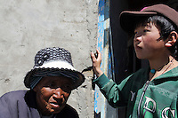 A Tibetan woman and child outside their home on the Tibetan Plateau, in western China.