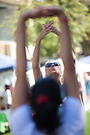Los Altos resident, Tanya De Mare, stretches during a free exercise class during the Los Altos Stride and Ride event on the State Street Green July 27.
