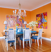The warm orange walls of the dining room are the ideal backdrop for a pair of abstract paintings by Jeremy Stenger and a photograph by Irene Mamiye