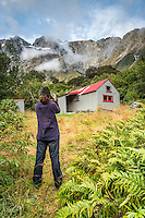 Tramper photographing Douglas Rock Hut in Copland Valley under Southern Alps, Westland National Park, West Coast, South Westland, World Heritage Area, New Zealand