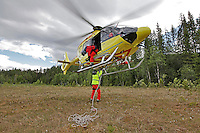 Rescue paramedic Asbjørn Møller attaches a rope, while doctor Steinar Einvik (in the door) guides pilot Viggo Jess Iversen during a training mission. Norwegian Air Ambulance operating EC 135 helicopter out of their base in Trondheim, one of eight bases operated by the company.