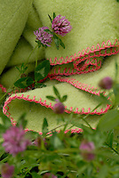 A pale green felt blanket is edged with a pink blanket stitch
