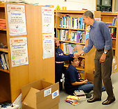United States President Barack Obama (R) greets volunteers in a library as he arrives to participate in a service project, at Browne Education Center, in Washington, DC, USA, on the Martin Luther King Jr national holiday, 16 January 2012. The project was in memory of the legacy of community service, promoted by the late civil rights leader, who was assassinated in 1968..Credit: Mike Theiler / Pool via CNP